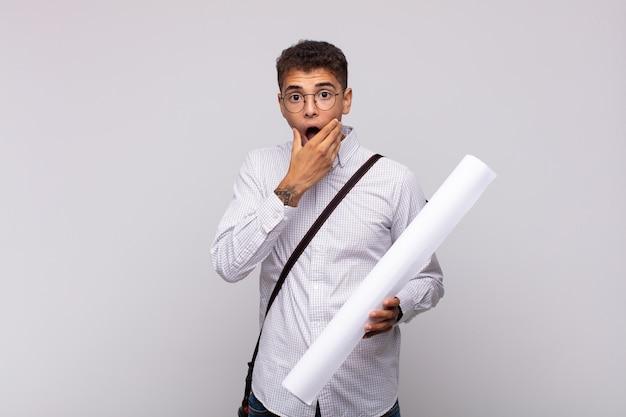 Junger architektenmann mit weit geöffnetem mund und augen und hand am kinn, der sich unangenehm schockiert fühlt und sagt, was oder wow