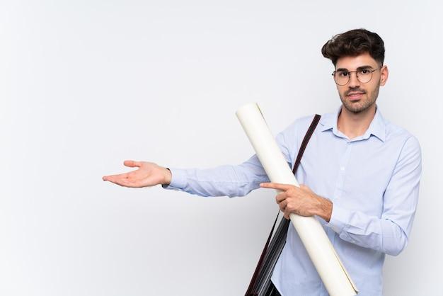 Junger architektenmann über ausdehnungshänden der lokalisierten weißen wand zur seite für die einladung zu kommen