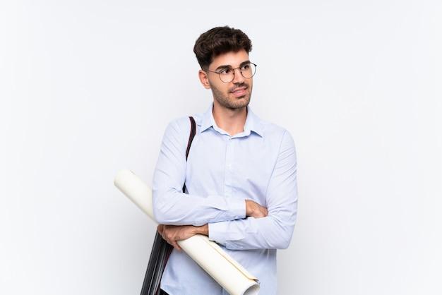 Junger architektenmann über der lokalisierten weißen wand, die zur seite schaut