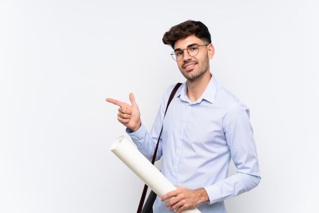 Junger architektenmann über lokalisierter weißer wand finger auf die seite zeigend