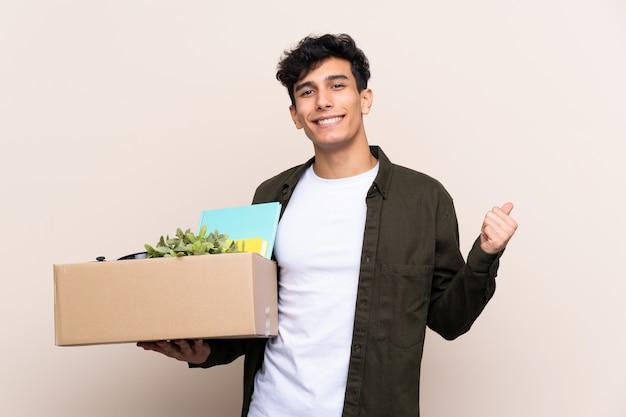 Junger argentinischer mann, der in neues haus über der lokalisierten wand zeigt auf die seite umzieht, um ein produkt darzustellen