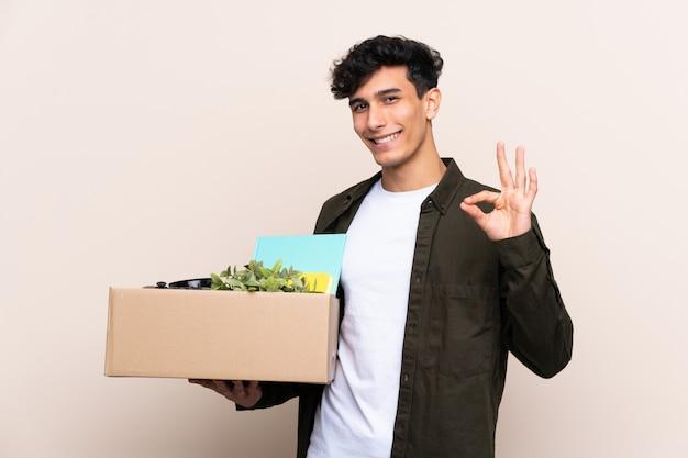 Junger argentinischer mann, der in neues haus über der lokalisierten wand zeigt okayzeichen mit den fingern umzieht