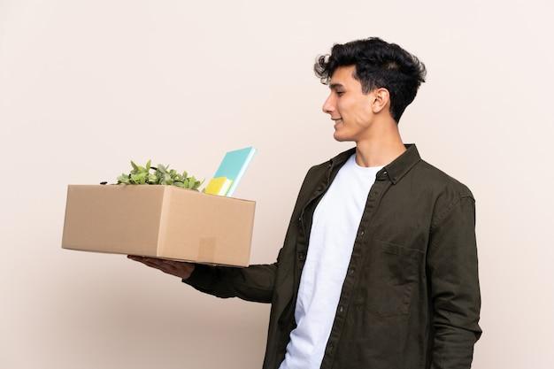 Junger argentinischer mann, der in neues haus über lokalisierter wand mit glücklichem ausdruck umzieht