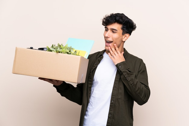 Junger argentinischer mann, der in neues haus über lokalisierter wand mit überraschung und entsetztem gesichtsausdruck umzieht