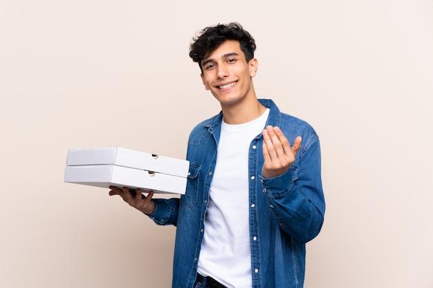 Junger argentinischer mann, der pizzas über der lokalisierten wand einlädt, mit der hand zu kommen hält. schön, dass sie gekommen sind