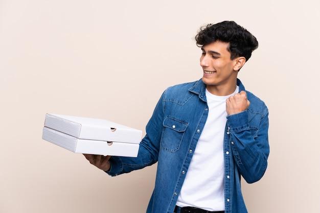 Junger argentinischer mann, der pizzas über der lokalisierten wand feiert einen sieg hält