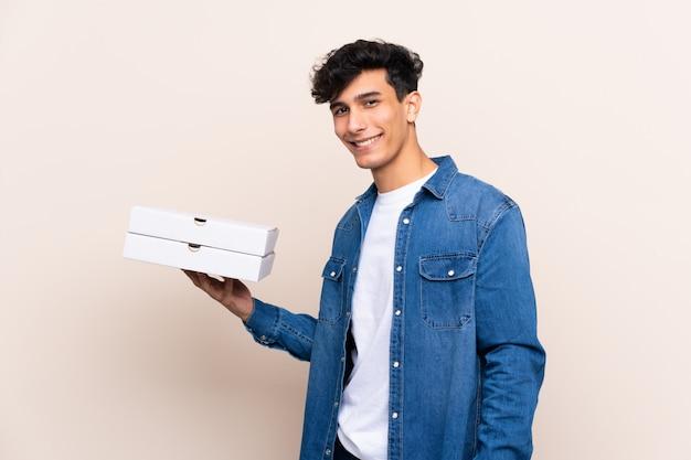 Junger argentinischer mann, der pizzas über der lokalisierten wand lächelt viel hält