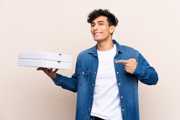 Junger argentinischer mann, der pizzas über lokalisierter wand hält und sie zeigt