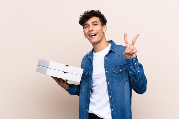 Junger argentinischer mann, der pizzas über lokalisierter wand lächelt und zeigt siegeszeichen hält