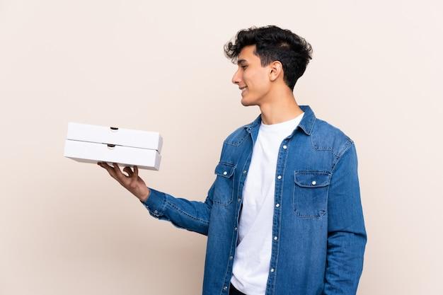 Junger argentinischer mann, der pizzas über lokalisierter wand mit glücklichem ausdruck hält