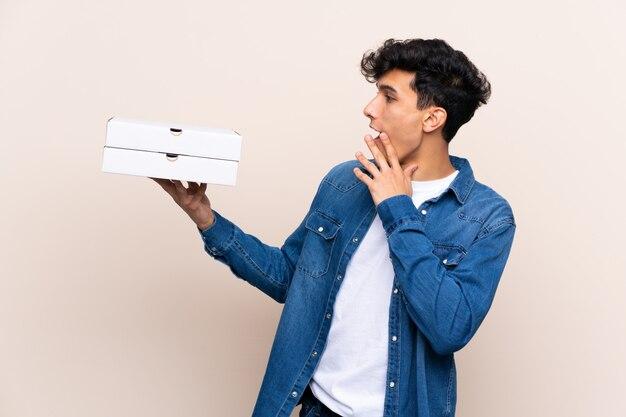 Junger argentinischer mann, der pizzas über lokalisierter wand mit überraschung und entsetztem gesichtsausdruck hält