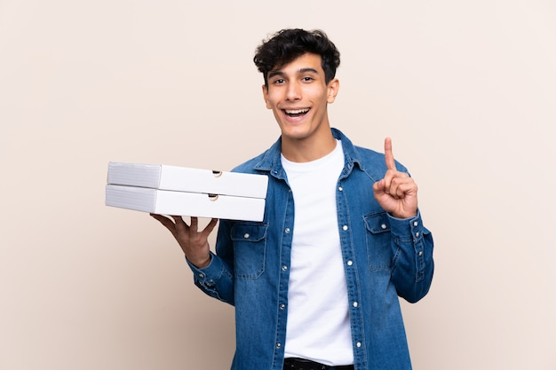 Junger argentinischer mann, der pizzas über lokalisierter wand oben zeigt eine großartige idee hält
