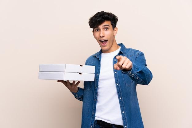 Junger argentinischer mann, der pizzas über lokalisierter wand überrascht hält und front zeigt