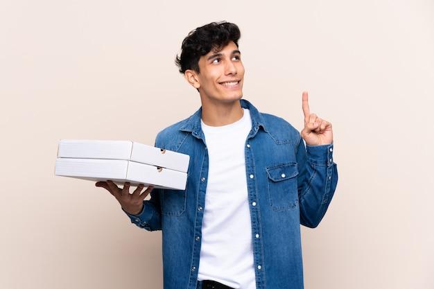 Junger argentinischer mann, der pizzen über der lokalisierten wand beabsichtigt, die lösung beim anheben eines fingers zu verwirklichen hält