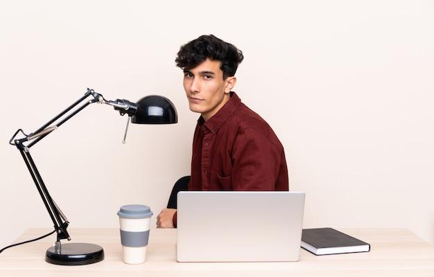 Junger argentinischer mann in einer tabelle mit einem laptop an seinem arbeitsplatz lachend