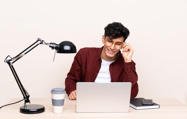 Junger argentinischer mann in einer tabelle mit einem laptop an seinem arbeitsplatz