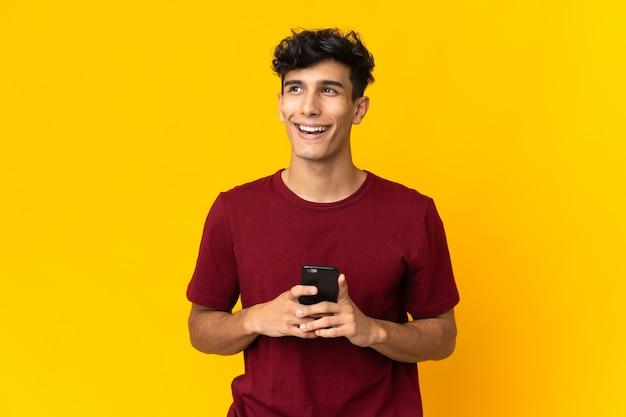 Junger argentinischer mann lokalisiert auf gelbem hintergrund unter verwendung von handy und nachschlagen