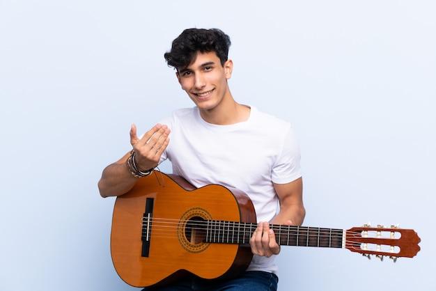 Junger argentinischer mann mit der gitarre, die einlädt, mit der hand zu kommen. schön, dass sie gekommen sind
