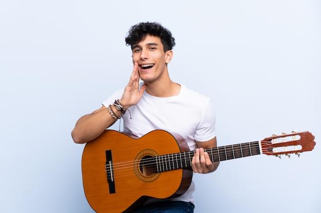 Junger argentinischer mann mit gitarre über der lokalisierten blauen wand, die mit dem breiten mund schreit, öffnen sich