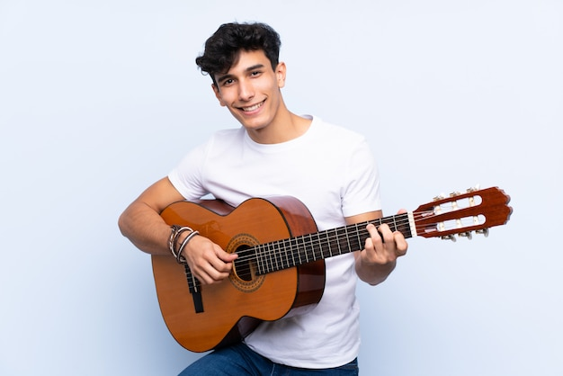 Junger argentinischer mann mit gitarre über getrennter blauer wand