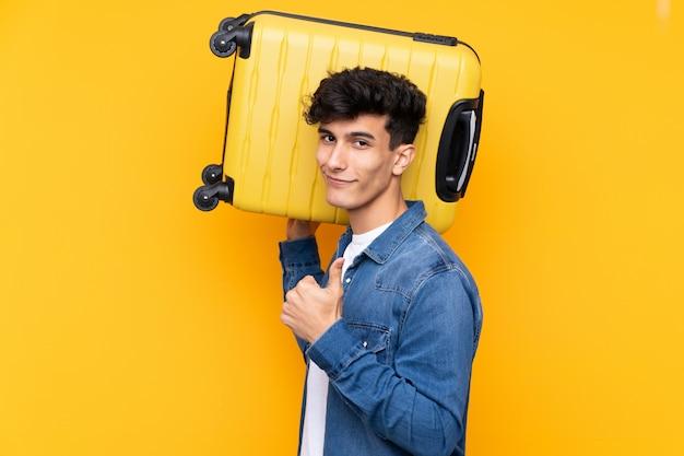 Junger argentinischer mann über lokalisierter gelber wand in den ferien mit reisekoffer und mit dem daumen oben