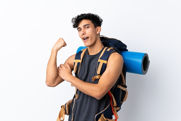 Junger argentinischer wanderermann über der lokalisierten weißen wand, die starke geste macht