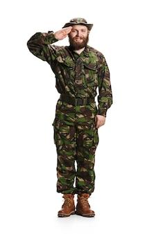 Junger armeesoldat, der tarnuniform trägt, die auf weißem studiohintergrund in voller länge steht und salutiert. junges kaukasisches modell. militär, soldat, armeekonzept. professionelle konzepte
