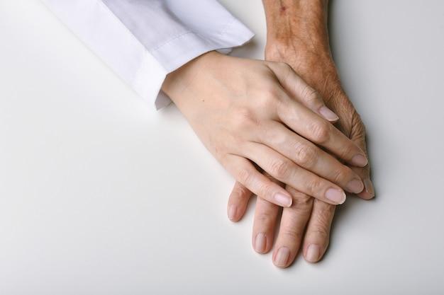 Junger arzt, der ältere patientenhand hält, um zu helfen und zu unterstützen