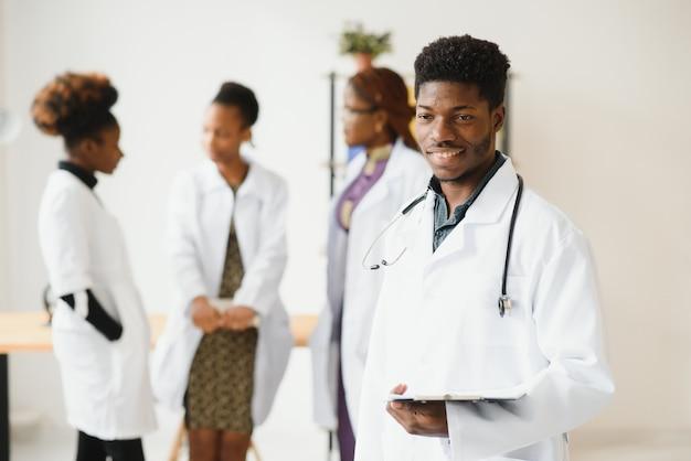 Junger arzt, der lächelt, während er in einem krankenhauskorridor mit einer vielfältigen gruppe von mitarbeitern steht