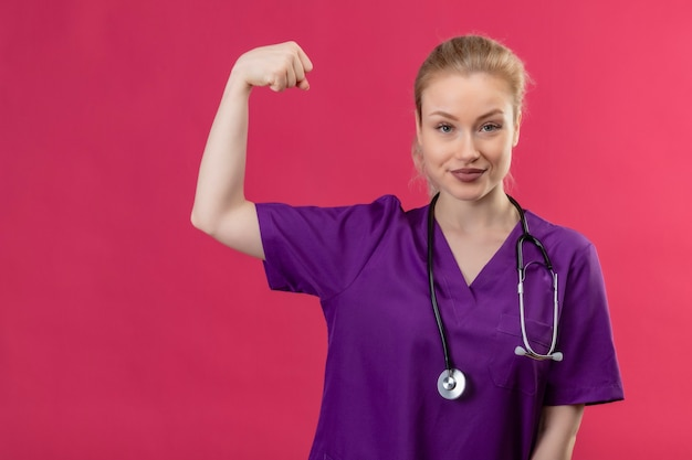 Junger arzt, der lila medizinisches kleid im stethoskop trägt, das starke geste auf isolierter rosa wand tut