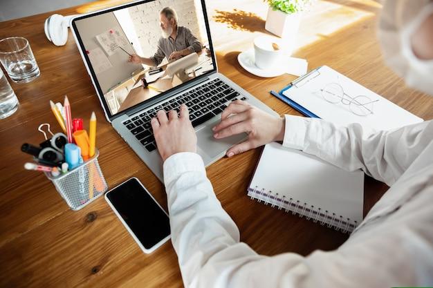 Junger arzt, der online mit laptop arbeitet, hat eine online-konferenz mit einem kollegen vom arbeitsplatz, der studiert. im gespräch mit patienten. coronavirus, covid-19-verhinderung der verbreitung von viren. ansicht von oben.