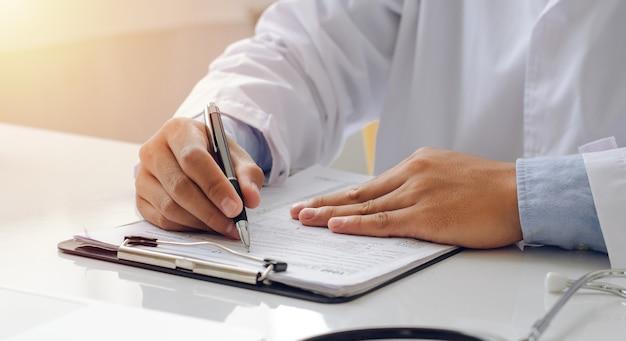 Junger arzt, der patienten eine behandlung verschreibt ein junger arzt mit einer formel zum schreiben mit einem stift, um den papierkram zu überprüfen. mit einem stethoskop im krankenhaus