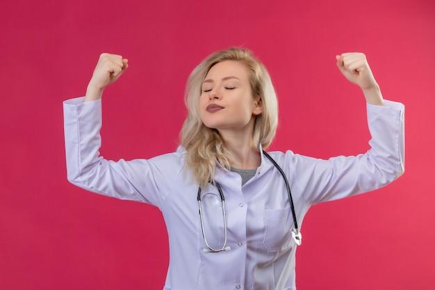 Junger arzt, der stethoskop im medizinischen kleid trägt und starke geste auf rotem hintergrund tut