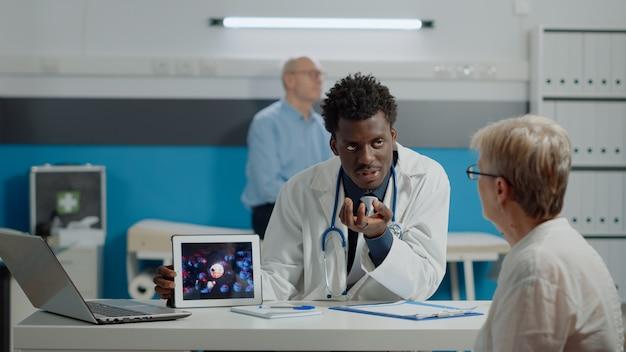 Junger arzt, der virusanimation auf tablet mit alter frau am schreibtisch im medizinischen kabinett analysiert. mediziner und ältere patienten, die ein modernes gerät betrachten, das coronavirus-bakterien und -gefahren zeigt