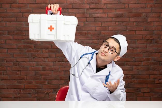 Junger arzt der vorderansicht im weißen medizinischen anzug mit erste-hilfe-kit