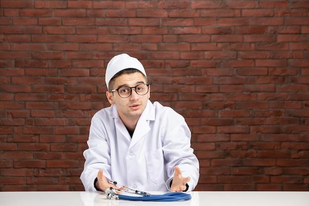 Junger arzt der vorderansicht im weißen medizinischen anzug