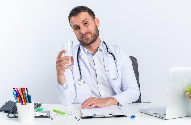 Junger arzt im weißen kittel und mit stethoskop, das ein glas wasser hält, glücklich und positiv lächelnd, selbstbewusst am tisch sitzend mit laptop über weißer wand
