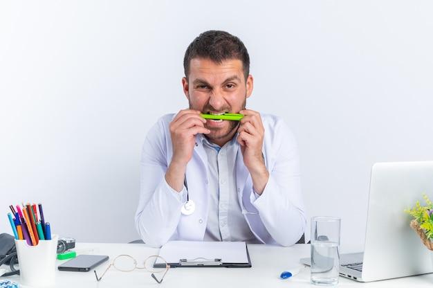 Junger arzt im weißen kittel und mit stethoskop, der gestresst und nervös beißt, sitzt am tisch mit laptop auf weiß