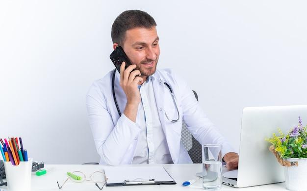 Junger arzt im weißen kittel und mit stethoskop lächelt fröhlich am tisch sitzend mit laptop, der am handy auf weiß spricht