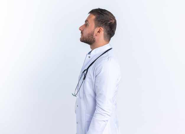 Junger arzt im weißen kittel und mit stethoskop um den hals, der selbstbewusst seitlich über der weißen wand steht?