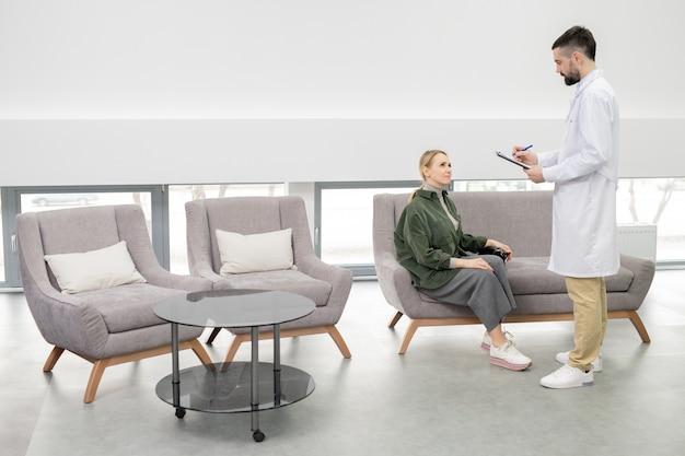 Junger arzt im weißmantel, der notizen macht, während er von patientin auf couch in der lounge der zeitgenössischen kliniken steht