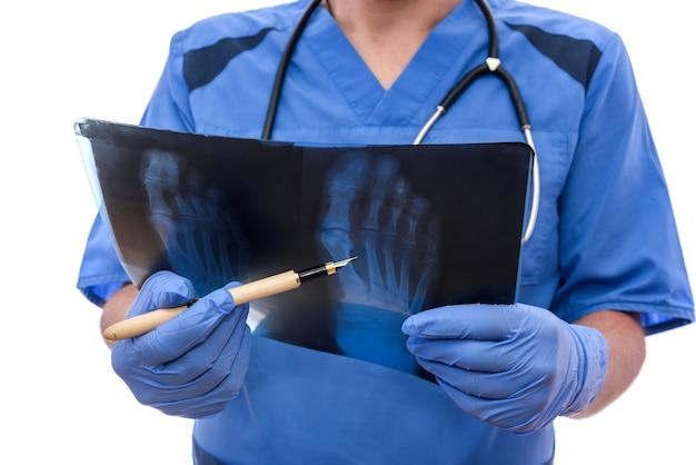Junger arzt in blauer uniform analysiert und zeigt dem patienten das problem. rheumatologe.