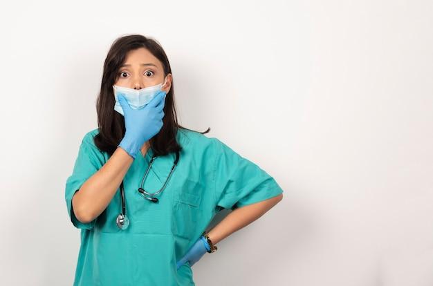 Junger arzt in der medizinischen maske und in den handschuhen, die auf weißem hintergrund aufwerfen. hochwertiges foto
