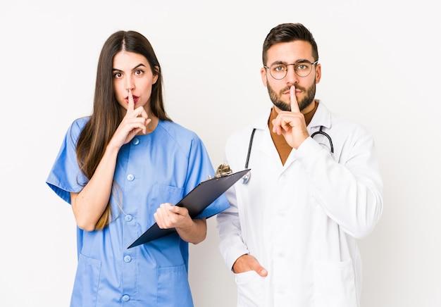 Junger arzt mann und eine krankenschwester isoliert, ein geheimnis zu halten oder um stille zu bitten.