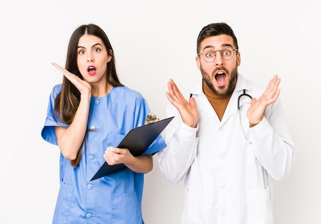 Junger arzt mann und eine krankenschwester isoliert überrascht und schockiert.