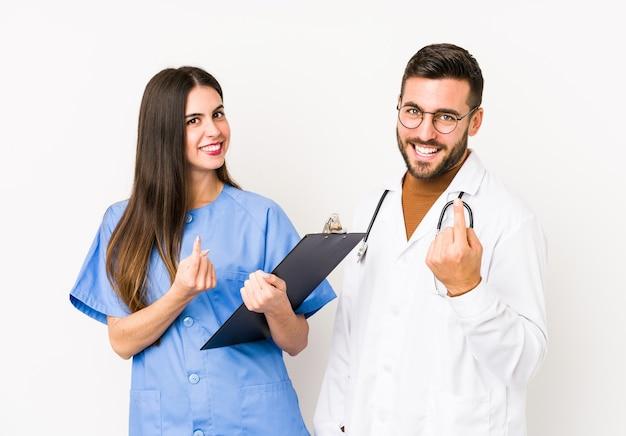 Junger arzt mann und eine krankenschwester isoliert zeigen mit dem finger auf sie, als ob einladend näher kommen.