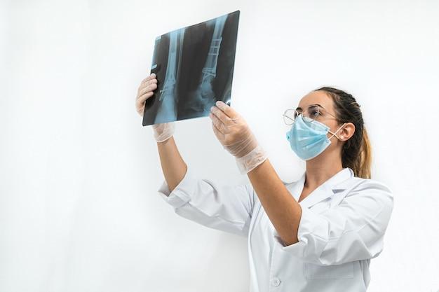 Junger arzt mit einer maske, die eine beinröntgenaufnahme untersucht