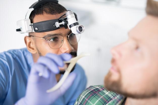 Junger arzt mit spezieller medizinischer ausrüstung auf dem kopf wird krankes ohr des patienten mit instrument untersuchen