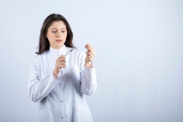 Junger arzt mit spritze, die sich auf die injektion an der weißen wand vorbereitet.