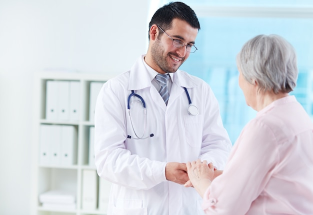 Junger arzt seinen patienten unterstützen